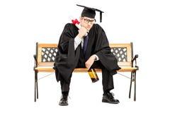 Sfrustowany męski uczeń sadzający na ławki mienia butelce piwo Zdjęcia Stock