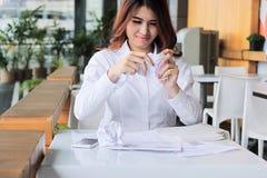 Sfrustowany młody Azjatycki mienie miący pracownika papier i uczucie stres przeciw jej pracie w biurze obraz royalty free
