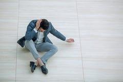Sfrustowany młody biznesmena obsiadanie na podłoga i patrzeć w dół fotografia stock