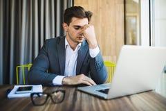Sfrustowany młody biznesowy mężczyzna pracuje na laptopie przy biurem Obraz Royalty Free