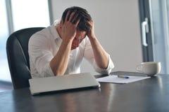 Sfrustowany młody biznesowy mężczyzna pracuje na laptopie w domu Obrazy Stock