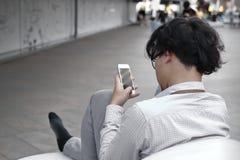 Sfrustowany niespokojny młody Azjatycki biznesowy mężczyzna używa mobilnego mądrze telefon przy outside biurem fotografia stock