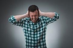 Sfrustowany przystojny mężczyzna zakrywa jego ucho stoi przeciw szaremu tłu z rękami zdjęcia stock