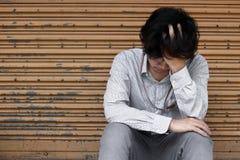 Sfrustowany zaakcentowany młody Azjatycki biznesowego mężczyzna nakrywkowy czoło z rękami i uczuciem rozczarowywającymi przy outs obrazy stock