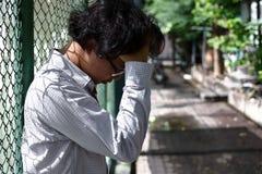 Sfrustowany zaakcentowany młody Azjatycki biznesowego mężczyzna uczucie rozczarowywający lub wyczerpujący z pracą przy outside bi zdjęcie stock