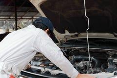 Sfrustowany zaakcentowany młody mechanika mężczyzna w bielu munduru uczuciu rozczarowywającym lub wyczerpującym z samochodem w ot fotografia royalty free