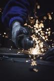 Sfuocato l'immagine del tubo del metallo di taglio del lavoratore dell'industria con sharp scintilla il fondo Immagine Stock
