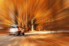 Sfuocatura delle automobili di viaggio della strada principale di autunno immagine stock libera da diritti