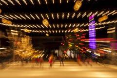 Sfuocatura delle luci di festa e dei pattinatori su ghiaccio Fotografie Stock Libere da Diritti
