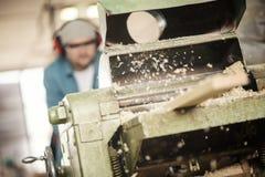 Såg den bitande wood plankan för mannen som använder den elektriska pimpeln Royaltyfri Fotografi