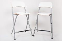Sgabelli alti bianchi in uno studio con il contesto grigio
