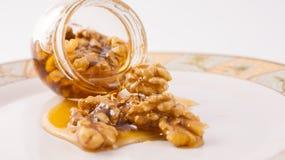 Sgocciolatura del miele e della noce dal barattolo Fotografia Stock