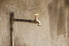 Sgocciolatura dell'acqua da un vecchio zipolo arrugginito Fotografie Stock
