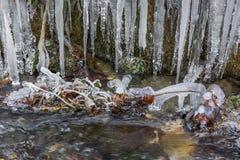 Sgocciolatura dell'acqua ghiacciata nel piccolo corso d'acqua del fiume fotografia stock