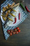 Sgombro al forno con il limone e le patate al forno su un piatto bianco Prodotto-verdure fresche di vegetables Ciliegia, peperonc fotografie stock