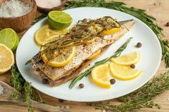 Sgombro cucinato su un piatto bianco con le spezie, le erbe, il limone, la limetta ed il sale Un primo piano, su un fondo di legn fotografie stock