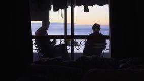 Sguardi dell'uomo e di una giovane donna all'alba del mare dal balcone dell'hotel e dal tè della bevanda stock footage