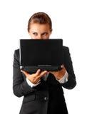 Sguardi sospettosi della donna di affari fuori dal computer portatile fotografie stock libere da diritti