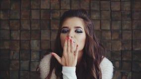 Sguardo castana della donna graziosa alla macchina fotografica e soffiare un bacio stock footage