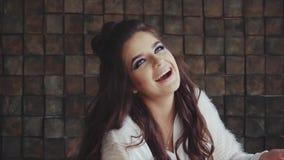 Sguardo castana della giovane donna graziosa alla macchina fotografica e risata istrionica stock footage