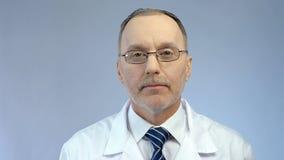 Sguardo con esperienza del medico maschio serio, aiuto medico professionale alla clinica Immagine Stock Libera da Diritti
