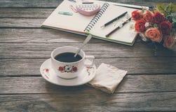 Sguardo d'annata del film: tazza di caffè con il taccuino Fotografie Stock