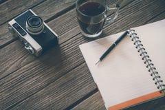 Sguardo d'annata del film: tazza di caffè con la macchina fotografica ed il taccuino Fotografie Stock Libere da Diritti