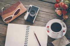 Sguardo d'annata del film: tazza di caffè con la macchina fotografica ed il taccuino Immagine Stock