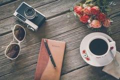 Sguardo d'annata del film: tazza di caffè con la macchina fotografica ed il taccuino Fotografia Stock Libera da Diritti