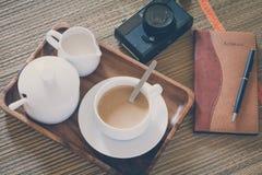Sguardo d'annata del film: tazza di caffè con la macchina fotografica ed il taccuino Immagini Stock