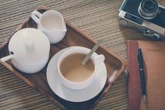Sguardo d'annata del film: tazza di caffè con la macchina fotografica ed il taccuino Fotografia Stock