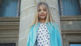 Sguardo da vicino alla macchina fotografica di sorridere, bambina sveglia a costruzione 4K archivi video