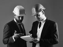 Sguardo degli appaltatori al piano della costruzione Gli architetti con i fronti seri discutono il progetto immagine stock
