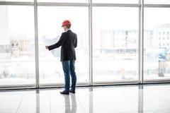 Sguardo del casco di sicurezza di usura dell'ingegnere del costruttore alla costruzione della carta di modello vicino alle finest Fotografia Stock