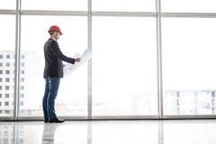 Sguardo del casco di sicurezza di usura dell'ingegnere del costruttore alla costruzione della carta di modello vicino alle finest Immagini Stock Libere da Diritti