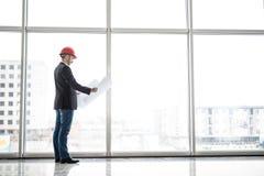Sguardo del casco di sicurezza di usura dell'ingegnere del costruttore alla costruzione della carta di modello vicino alle finest Immagine Stock
