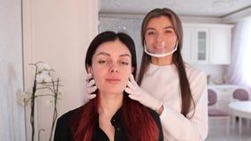 Sguardo del cliente e del truccatore alle sopracciglia dipinte nello specchio Le ragazze stanno preparando per trucco permanente  archivi video