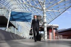 Sguardo del lavoro di viaggio dell'uomo di affari il bordo del segno che cammina con il carrello dei bagagli Fotografie Stock Libere da Diritti