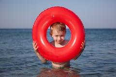Sguardo del ragazzino dall'anello gonfiabile nel mare fotografie stock
