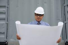 Sguardo del responsabile dell'ingegnere al piano della carta di consturction Immagini Stock Libere da Diritti