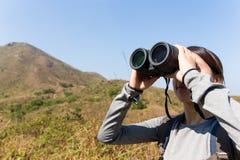 Sguardo della donna comunque binoculare quando escursione andante Fotografia Stock Libera da Diritti