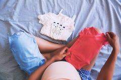 Sguardo della donna incinta dei vestiti del bambino immagine stock