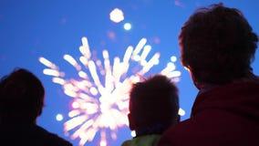 Sguardo della famiglia al cielo ai fuochi d'artificio Il cielo notturno alle luci stock footage