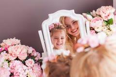 Sguardo della figlia e della madre allo specchio fotografia stock