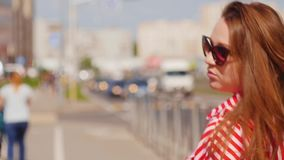 Sguardo della giovane donna del ritratto alla macchina fotografica e camminare al centro urbano Chiuda sul colpo archivi video
