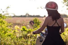 Sguardo della ragazza nello specchietto retrovisore sul motorino fotografie stock