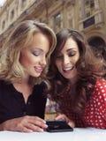 Sguardo delle amiche ai telefoni cellulari Immagine Stock