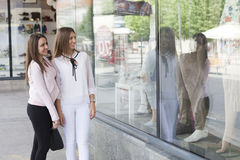 Sguardo di due un bello giovani donne in una finestra di deposito Fotografie Stock Libere da Diritti