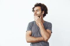 Sguardo di pensiero dell'uomo africano incerto nel lato sopra la parete bianca, decidente se comprare alcuni aggeggi online o uno Immagine Stock Libera da Diritti