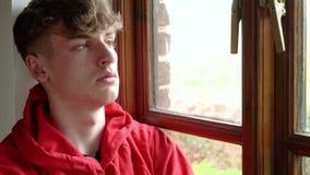 Sguardo di seduta dell'adolescente dell'adulto maschio teenager depresso triste del giovane da una finestra video d archivio